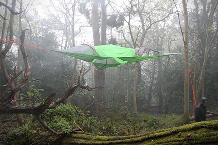 ein-grünes-touristisches-zelt-mit-einem-leiter-in-dem-wilden-wald