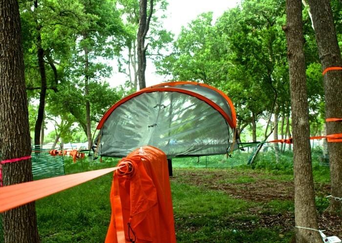 ein-oranges-campingzelt-im-grünen-wald