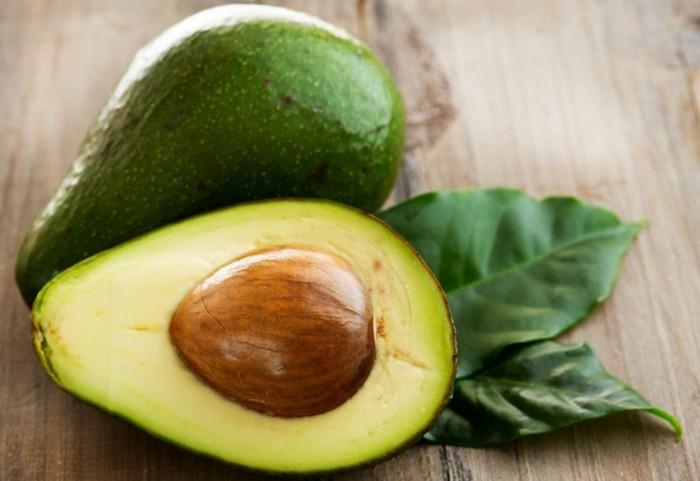 gesichtsmaske-selber-machen-avocado-grüne-blätter-hölzerner-tisch-gesundheit-pflege