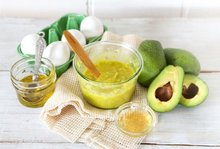gesichtsmasken-eier-löffel-avocado-honig-glaschale-weißer-tisch-tuch-oil
