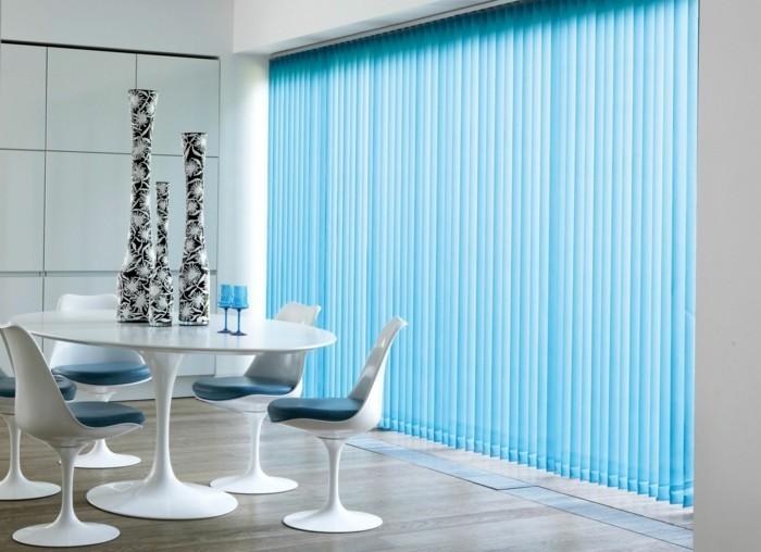 himmelblaue-maßgefertigte-jalousien-vasen-boden-aus-holz-weißer-tisch-stühle-weingläser