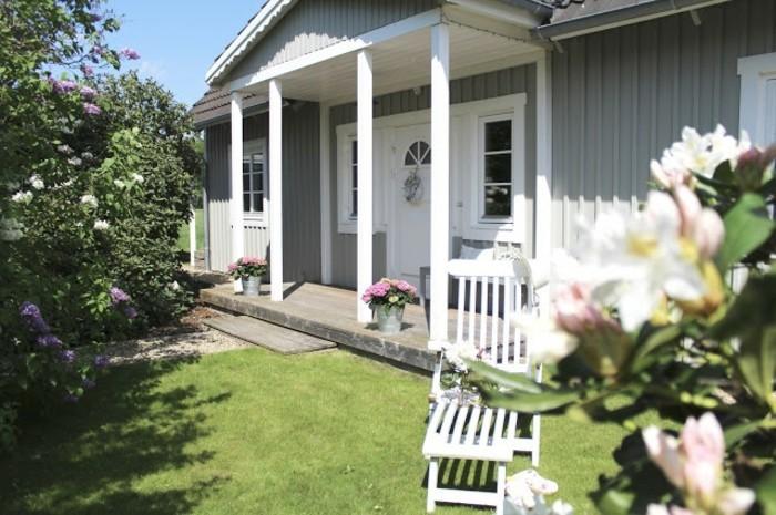 holzhaus-mit-veranda-frühling-frische-rasenfläche