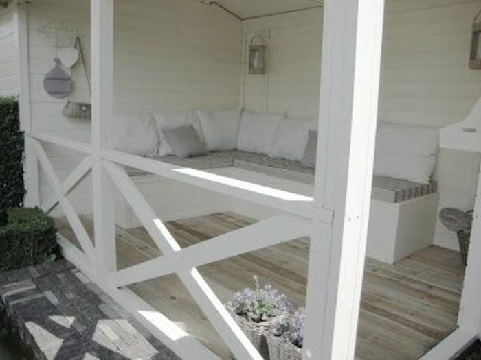 holzhaus-mit-veranda-weiß-lackiert-sitzecke-mit-kissen