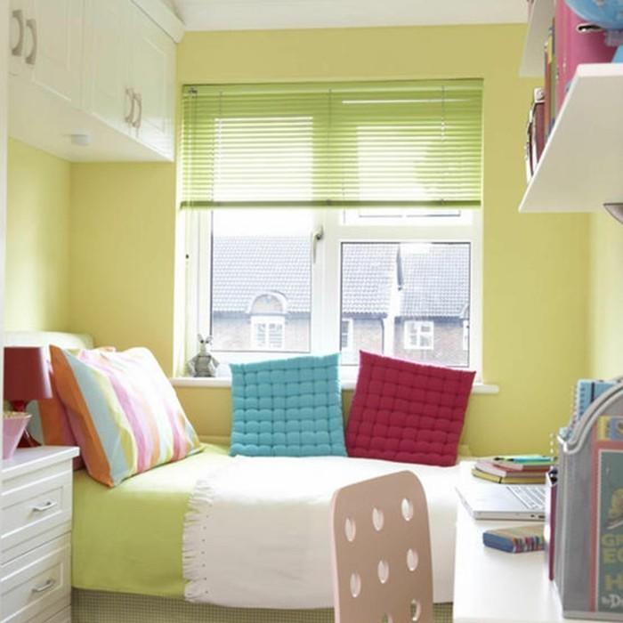 ideen-kinderzimmer-klein-grün-regal-über-schreibtisch-kommode-weiß-bett-vor-fenster-bunte-kissen