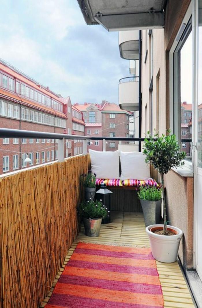 ideen-kleiner-balkon-grüne-pflanzen-retro-teppich-in-rosa-und-orange-kleiner-sofa