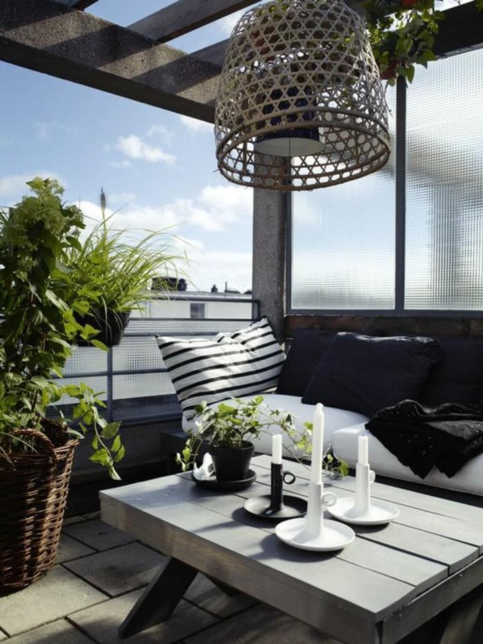ideen-kleiner-balkon-tisch-aus-holz-weiße-kerzen-sofa-kissen-geflochtener-korb-lampenschirm-himmel
