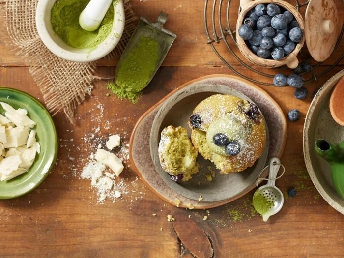matcha-kuchen-minikuchen-muffin-mit-matcha-blaubeeren-deko-auf-dem-tisch-beim-backen