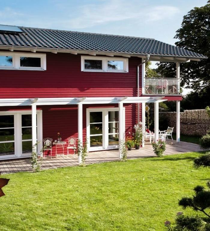 mehrstockiges-holzhaus-mit-veranda-und-frische-rasenfläche