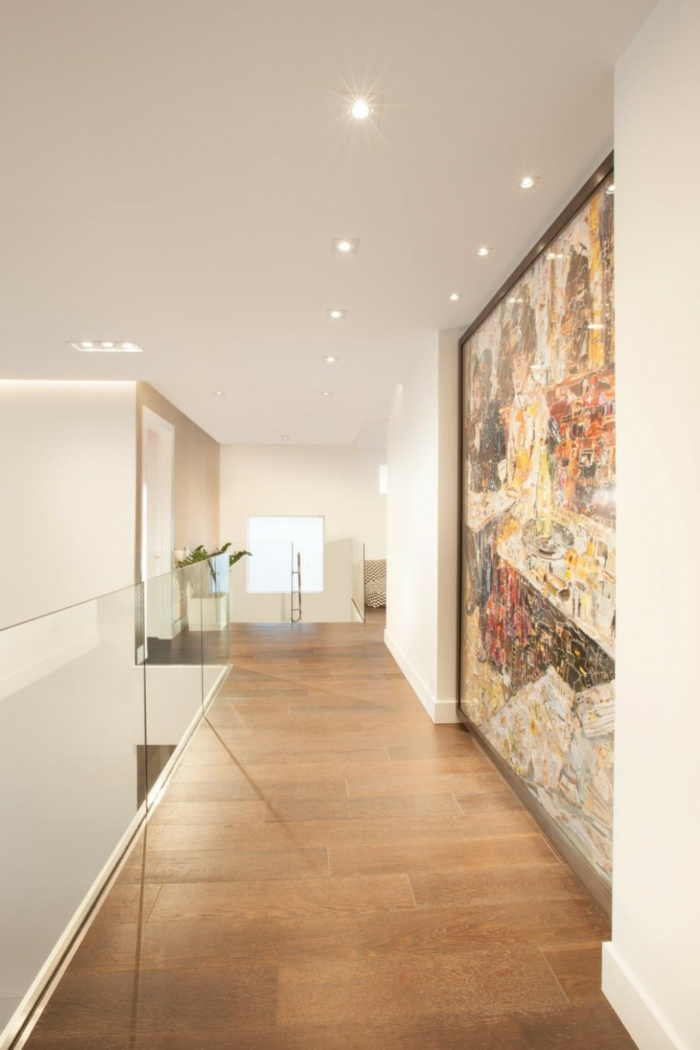 moderne-flurgestaltung-mit-einem-großen-abstrakten-bild-an-der-ganzen-wand-laminatboden-deckenleuchte