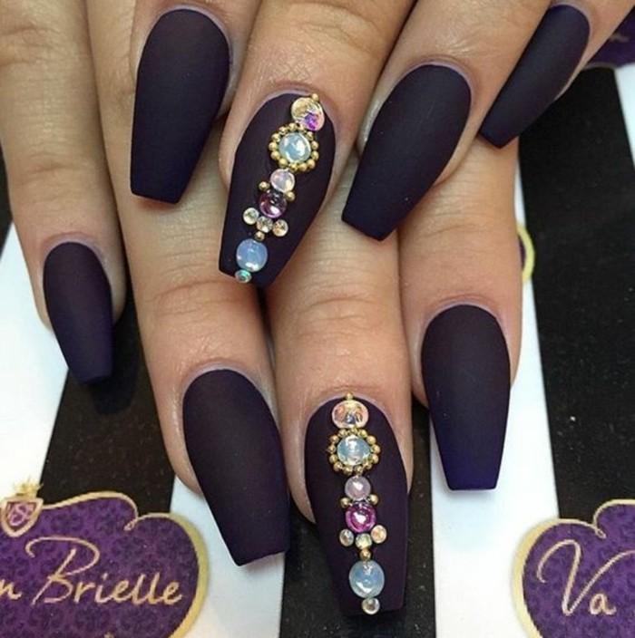 naegel-mit-steinchen-dunkel-lila-matt-farbe-nagellack-stein-dekoration-bunte-steine-als-nageldeko-ideen