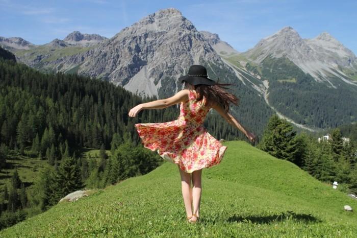 reiselustige-frau-gebirge-schoene-natur-naturfreunde-tanzen-buntes-kleid-lange-haare