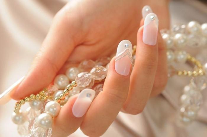 schoene-fingernaegel-bilder-lange-naegel-french-mit-steinen-perlen-in-der-hand