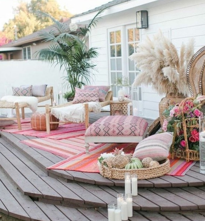 terrassengestaltung-ideen-grüne-pflanze-weiße-kerzen-boden-aus-holz-rosa-kissen-rosen-geflochtene-körbe