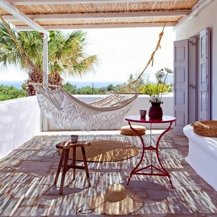 terrassengestaltung-ideen-hut-runder-tisch-hocker-weiße-hängematte-palme-blumen