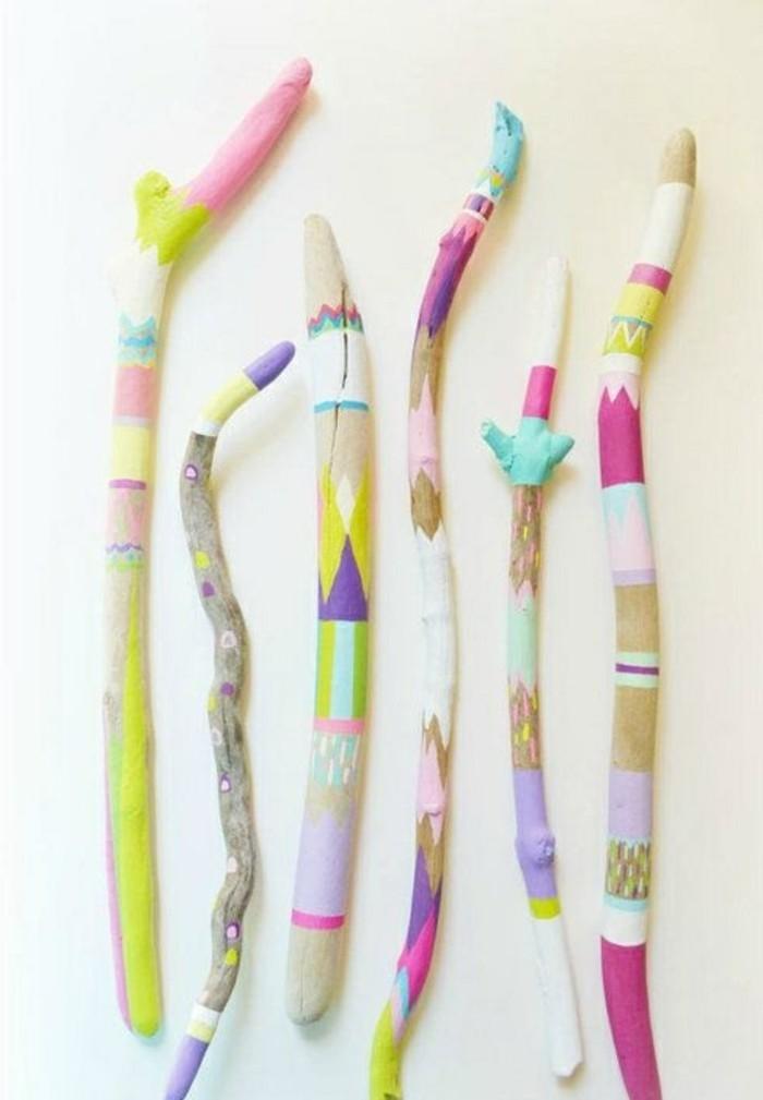 treibholz-basteln-aeste-mit-bunten-farben-bemalen-weisse-wand-dekoration