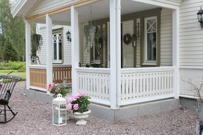 weißes-holzhaus-mit-veranda-gartendeko-landhausstil