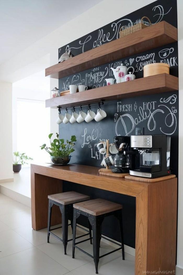 wohnungdeko-schwarze-tafel-hölzerner-tisch-stühle-pflanze-kaffeemaschine-fliesen-regale-tassen