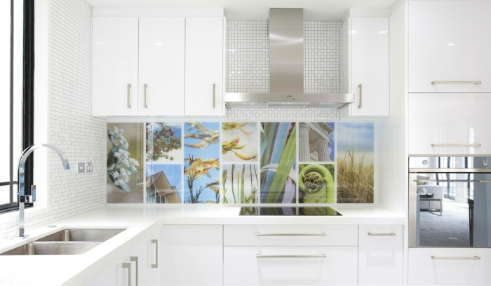 eine weiße küche mit buntem küchenrückwand als akzent