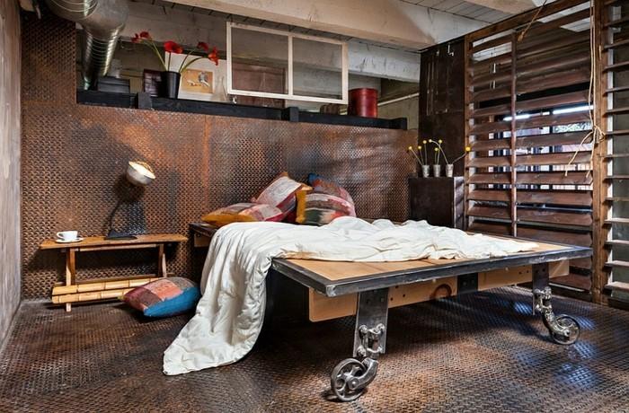 10industrialdesign-möbel-doppelbett-rädern-holz-metall-bunte-kissen-trennwand-holz-weiße-schlafdecke