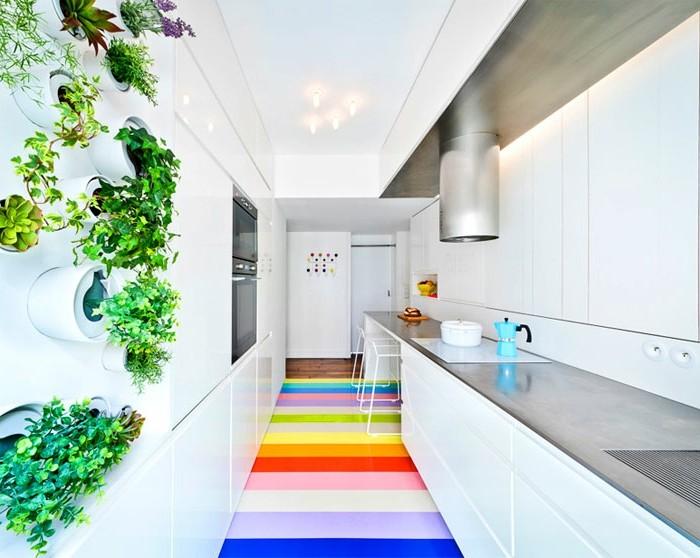 weiße-küchenfronten-bunte-streifen-boden-weiße-küchenschranktüren-graue-tischplatte-abzugshaube-pflanzenwand