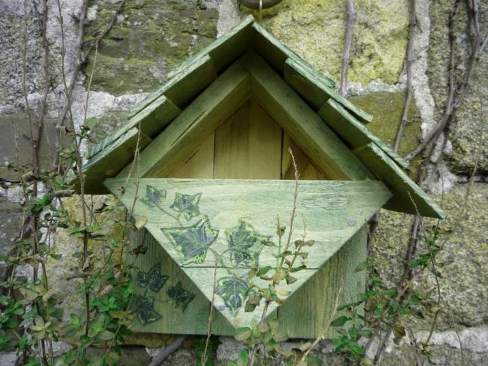 grünes Holzhäuschen für Vögel, montiert an Natursteinmauer