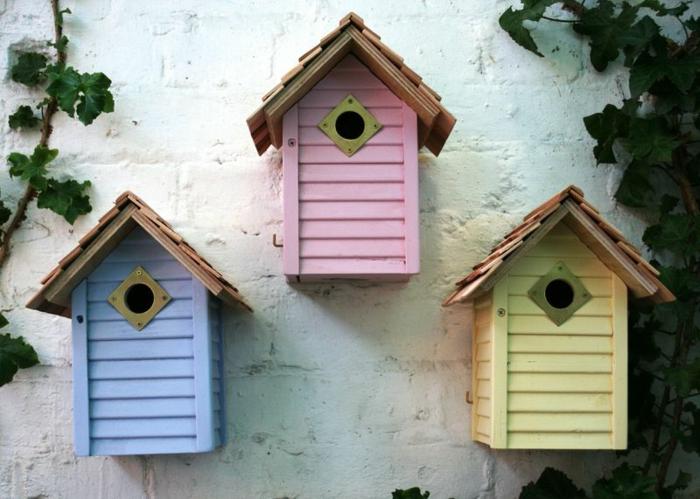 Vogelhäuser in blauer, pinker und gelber Farbe