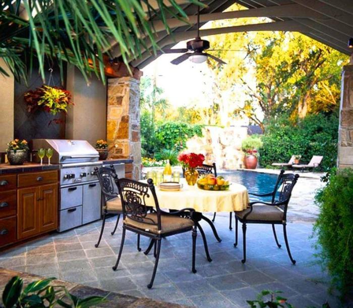 Outdoor Grillküche mit rundem Esstisch mit Schwimmbadaussicht