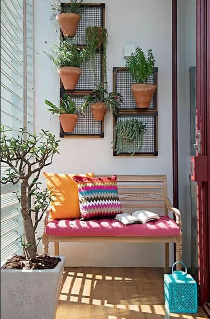 2schmalen-balkon-gestalten-glastür-roter-rahmen-pflanzendeko-sitzbank-holz-bunte-kisse-orange-kisse-rote-kisse