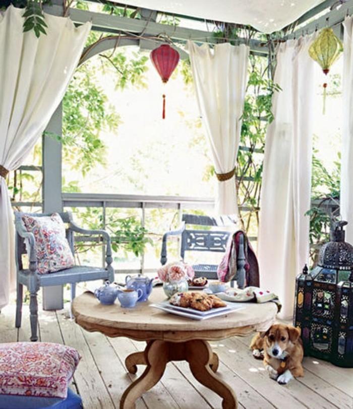 3schmalen-balkon-gestalten-holzboden-holztisch-rund-vintage-holzstühle-blau-antik-vorhänge-weiß-balkondeko