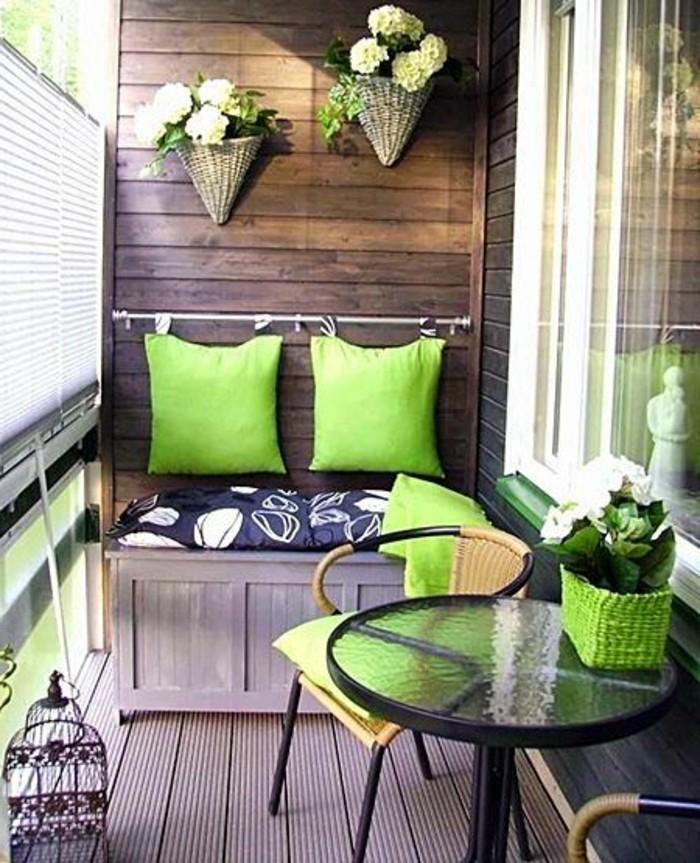 4kleine-räume-geschickt-einrichten-balkon-verglasen-grüne-kissen-holzboden-glastisch.flechtstühle-holzewand