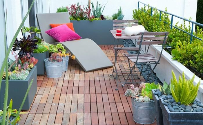 5schmalen-balkon-gestalten-liegestuhl-holzboden-steindeko-holzmöbel-rote-kisse-orange-kisse-kakteen
