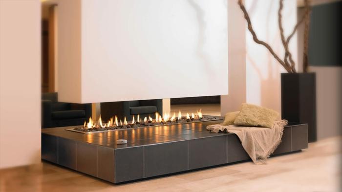 7offener-kamin-steine-verkleidung-schwarze-fliesen-laminatboden-ikebana-dekorative-vase-schwarze-couch