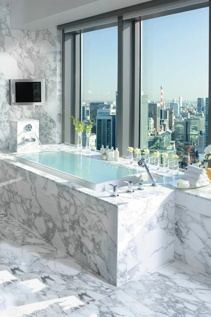 stilvolles badezimmer mit eckiger badewanne und fernseher