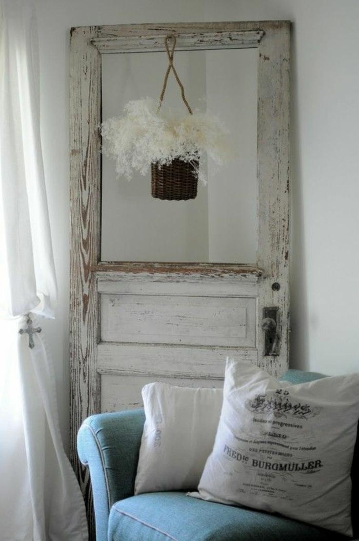 Alte-tür-deko-in-weißer-farbe-mit-hängenden-blumentopf-hinter-blaues-sofa