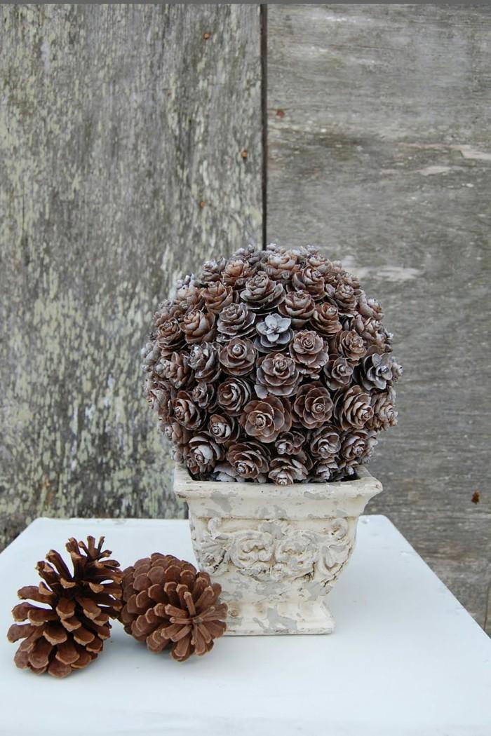 Deko-tannenzapfen-wie-blumen-in-einer-weißen-vase