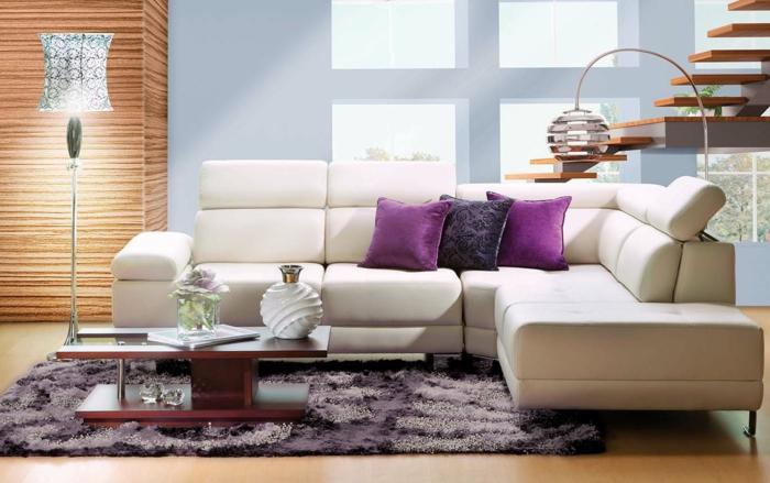 Modernes-Wohnzimmer-lila-Dekokissen-Teppich-Kaffeetisch-Lampe-Fenster-Weißer-Ecksofa