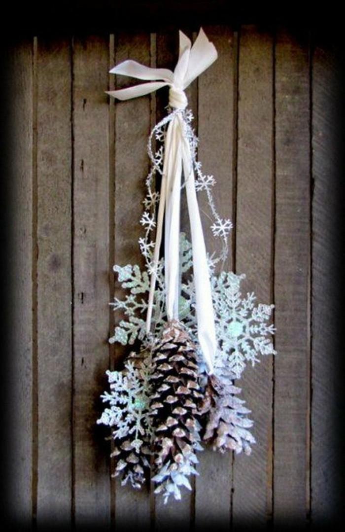 Tannenzapfen-deko-schneeflocken-auf-weißem-band-hängend
