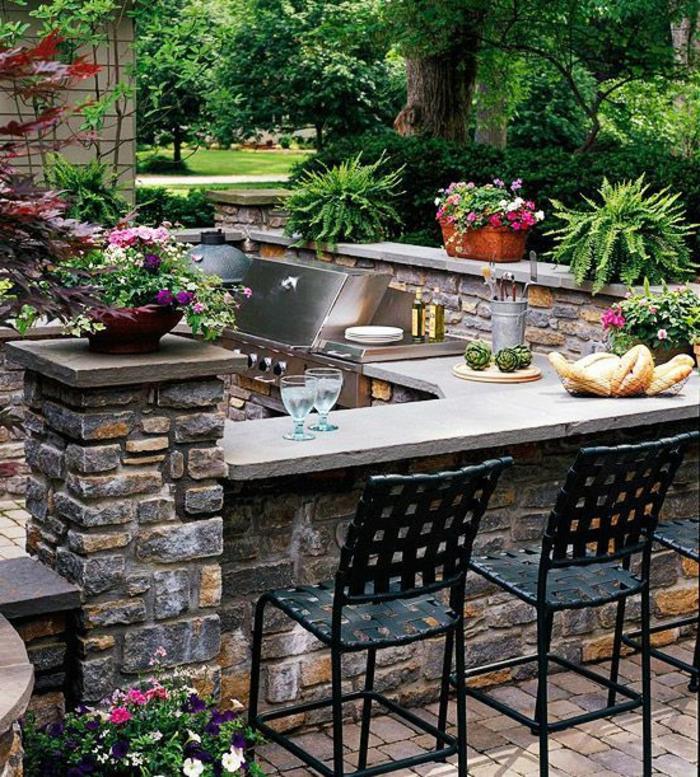 schön gestaltete Gartenküche mit Grill und Eckbar