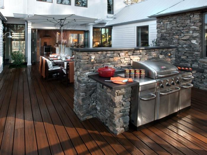 Terrassenküche mit Grill und einer optischen Raumtrennung