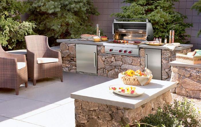 gemauerte Gartenküche aus Naturstein, komfortable Flechtstühle