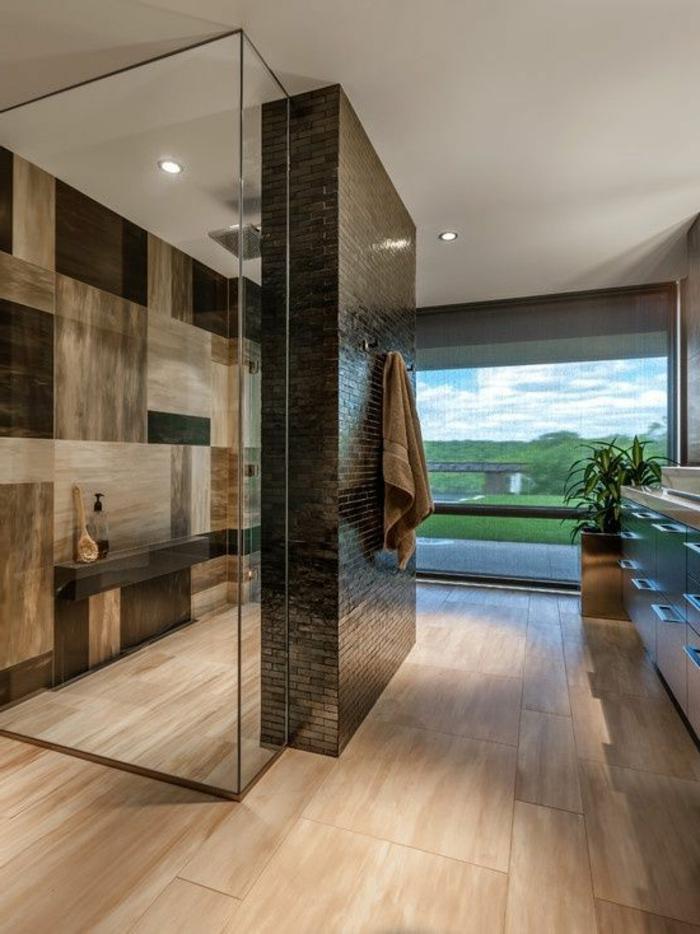 schönes badezimmer in braun mit duschkabine und einem großem fenster