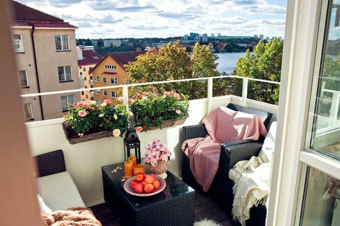 balkon-deko-flechtmöbel-schwarz-weiße-schlafdecke-pinke-schlafdecke-obst-kerzen-pflanzen-blumen-holzboden