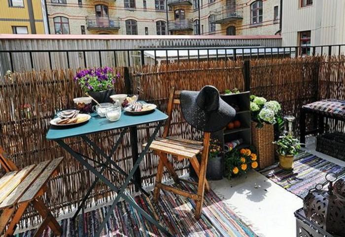 balkon-deko-musterteppiche-holzgeländer-blauer-tisch-holzstuhl-sitzbank-tischdeko-schwarzer-regal