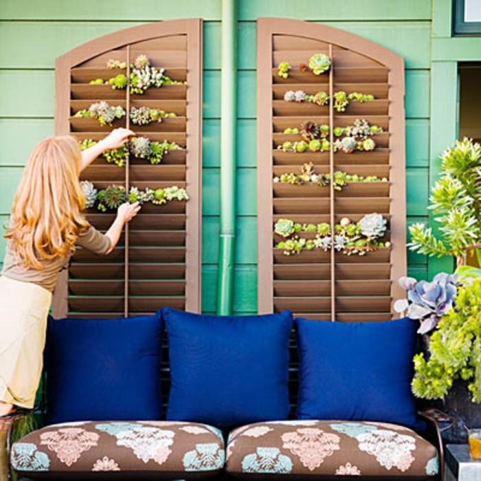 balkon-deko-pflanzenwand-couch-blaue-kissen-kissen-musterbezug-grüne-holzwand