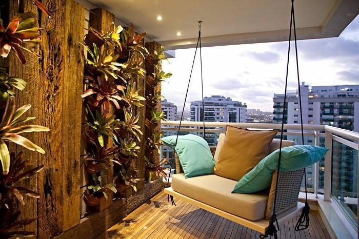 balkon-ideen-hängende-schauckelcouch-blaue-kissen-orange-kisse-holzboden-pflanzenwand-glasgeländer