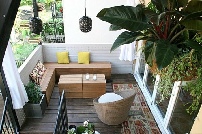 balkon-ideen-holzmöbel-holzboden-musterteppich-holzzaun-treppen-gelbe-kissen-weiße-kerzen-pflanzen