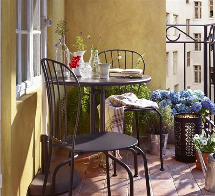 balkongestaltung-braune-bodenfliesen-metallstühle-schlafdecke-tischdeko-pflanzen-vasen-blumen