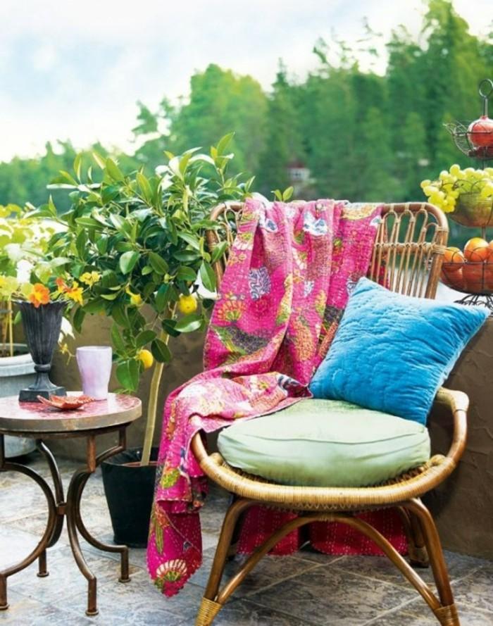 balkongestaltung-flechtstuhl-bodenfliesen-grüne-kisse-bunte-schlafdecke-blaue-kisse-runder-tisch-metallbeine