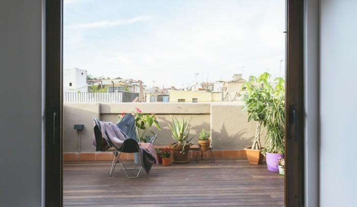 balkongestaltung-holzboden-klappstuhl-grüne-pflanzen-schlafdecke