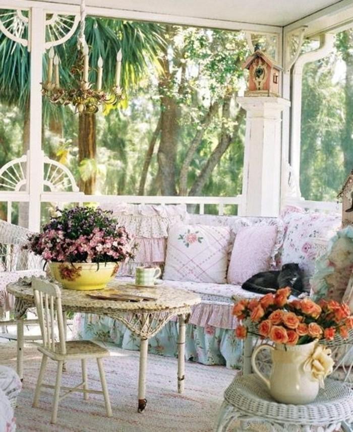 balkongestaltung-mediterran-barock-stil-runder-tisch-flechttisch-kleine-holzstühle-blaue-couch-kissen